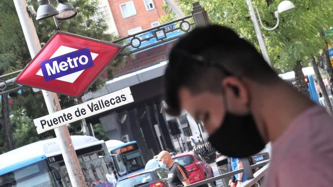 Vecinos pasean al lado del metro de Puente de Vallecas, en Madrid