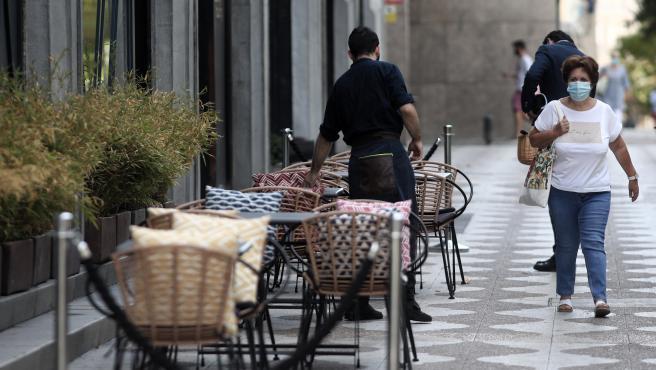 Un camarero prepara una terraza de un bar en Madrid.