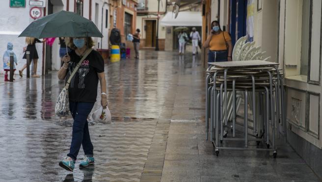 Una mujer se protege de la lluvia bajo su paraguas.
