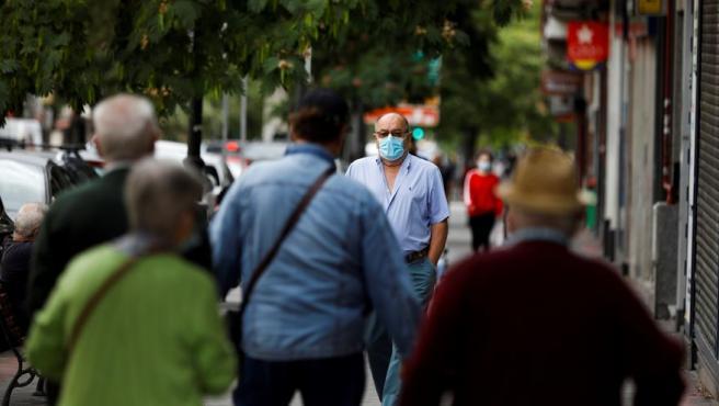 Imagen de varias personas paseando con mascarilla.