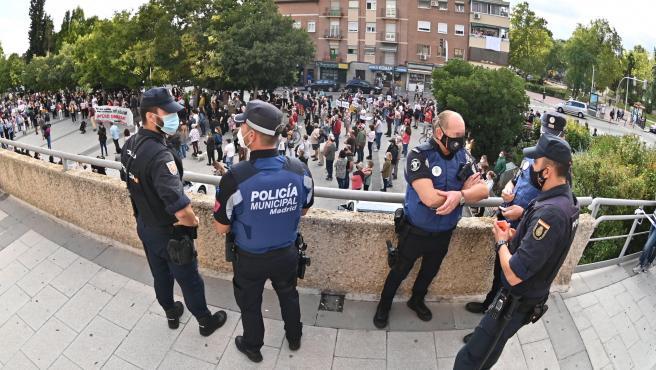 Agentes de la Policía Nacional y Local durante una manifestación de protesta en el distrito de Usera contra el confinamiento del sur de Madrid.