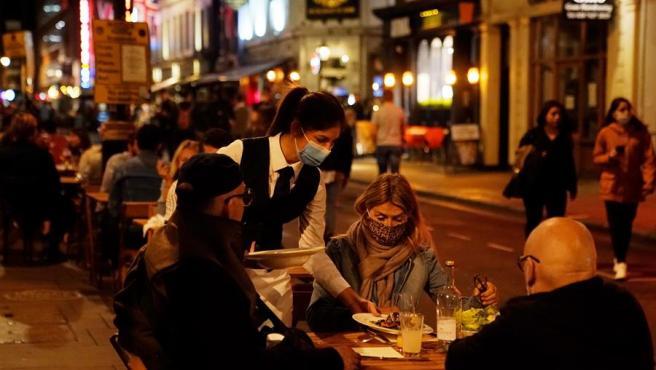 Una camarera con mascarilla por el coronavirus atiende una mesa en una terraza de un restaurante en Londres, Reino Unido.