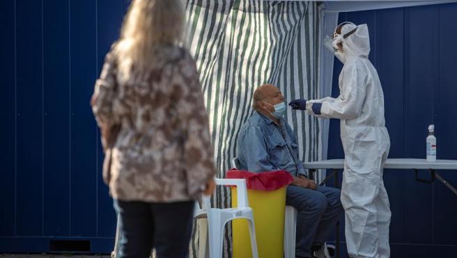 Un sanitario toma una muestra a un hombre en una estación de test de Covid en Praga, República Checa.