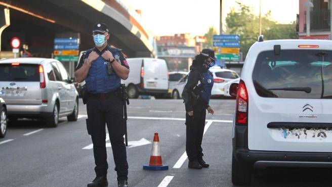 Un agente de la Policía Municipal de Madrid pide la documentación a un conductor, en un control junto al Puente de Vallecas, una de las zonas con movilidad restringida por el coronavirus.