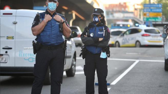 Dos policías permanecen atentos a todos los vehículos que circulan junto a un control situado en el Puente de Vallecas, una de las zonas confinadas por coronavirus en Madrid.