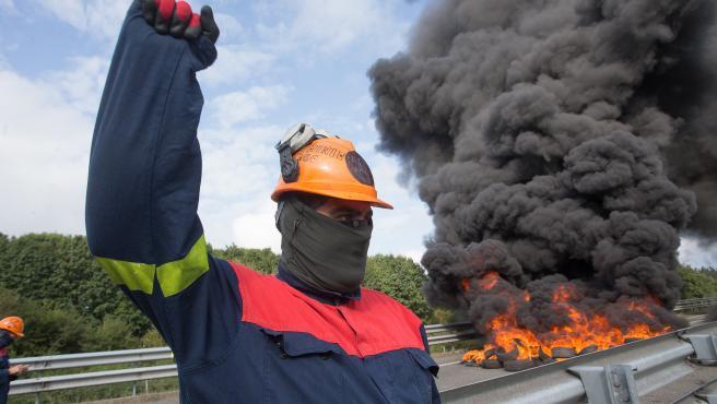 Outeiro de Rei, Lugo. Trabajadores de Alcoa cortan la A6 en ambos sentidos para reivindicar la permanencia de la factoria de aluminio en San Cibrao. En la imagen, un obrero alza el puno frente a una barricada en la manana del martes 22 de septiembre