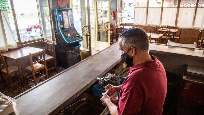 Un camarero seca varios vasos en un bar