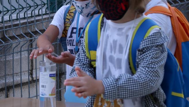 Dos alumnos de primaria se lavan las manos con gel hidroalcohólico en la puerta del colegio, el primer día de curso en Tortosa.