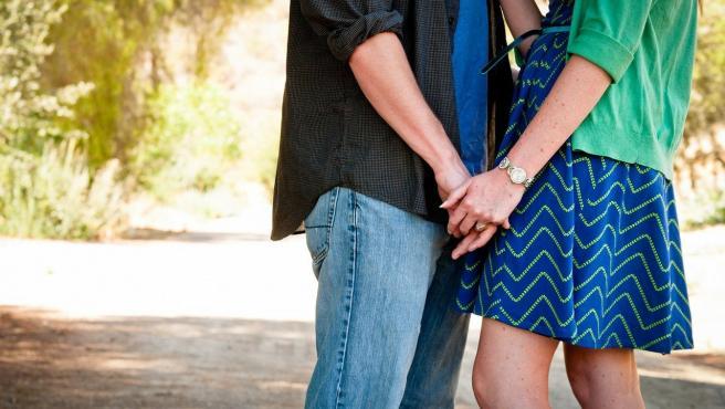 Una pareja se agarra de las manos.
