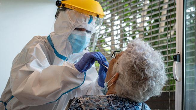 Una paciente se realiza una PCR para saber si es positiva en coronavirus, en un centro de atención primaria en Palamós (Girona).