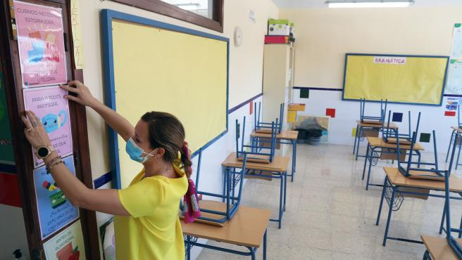 Una profesora coloca carteles de medidas preventivas ante la Covid-19 en el aula en un colegio.