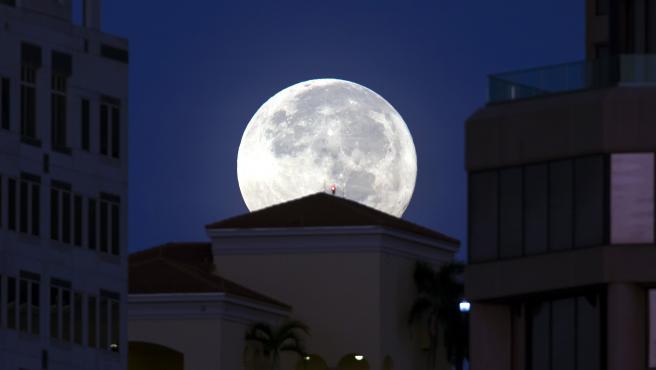 La Luna llena asoma por encima de los edificios en West Palm Beach (EE UU).