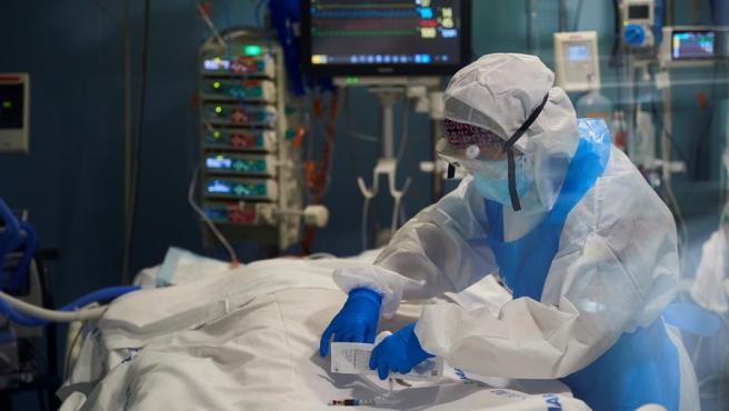 Un profesional sanitario toma una muestra de sangre a un enfermo de Covid-19 en la UCI del hospital del Mar de Barcelona.
