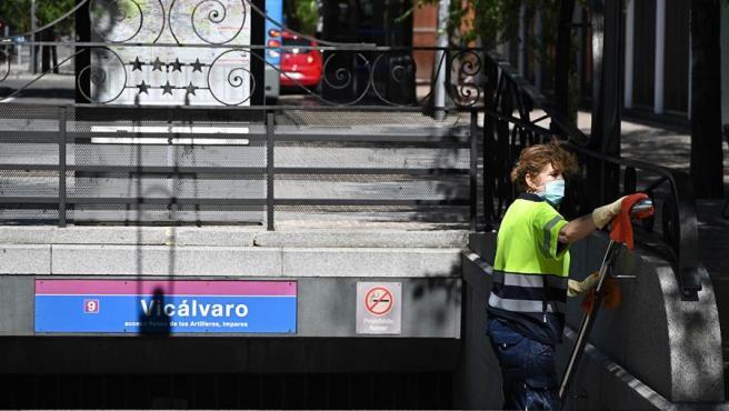 Una trabajadora limpia un acceso al metro en el distrito de Vicálvaro, en una de las 8 nuevas zonas de Madrid con restricciones de movilidad por el coronavirus.