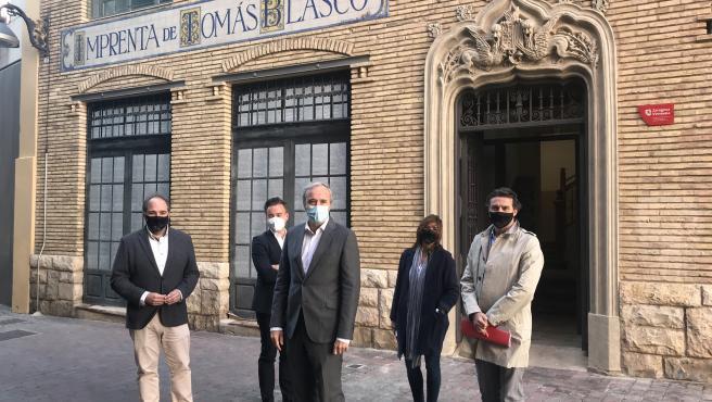 El alcalde de Zargoza, Jorge Azcón; el consejero municipal de Urbanismo, Víctor Serrano; y concejal delegada de Vivienda, Carolina Andreu; delante del edificio reahabilitado de la Imprenta Blasco