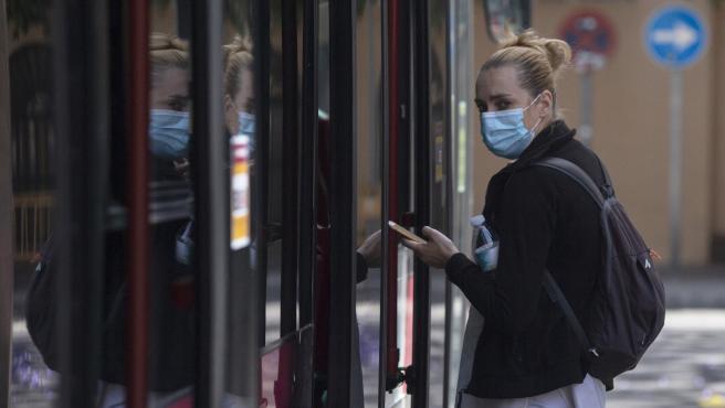 Una pasajera protegida con mascarilla antes de subir a un autobús de Tussam