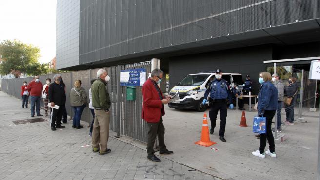 Vecinos del Puente de Vallecas, en Madrid, aguardan turno para ser sometidos al test de antígenos para detectar la Covid.