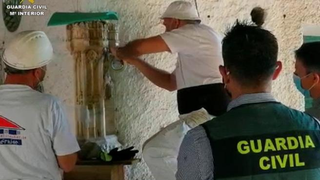 Operarios manipulando la pieza, encastrada en una esquina de la fachada de una finca agrícola.