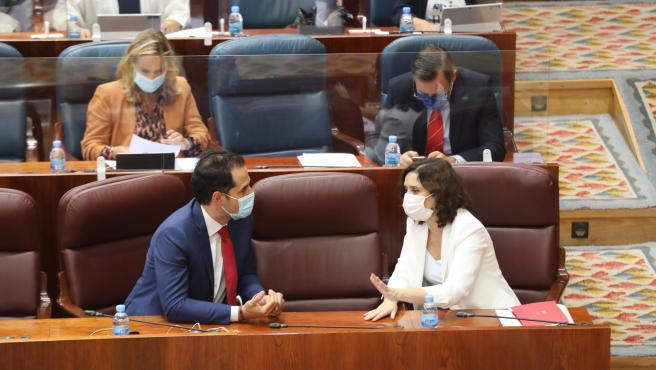 La presidenta de la Comunidad de Madrid, Isabel Díaz Ayuso, habla con el vicepresidente de la Comunidad, Ignacio Aguado, durante una sesión plenaria en la Asamblea de Madrid, en Madrid (España) a 1 de octubre de 2020. El Gobierno regional aprueba en esta