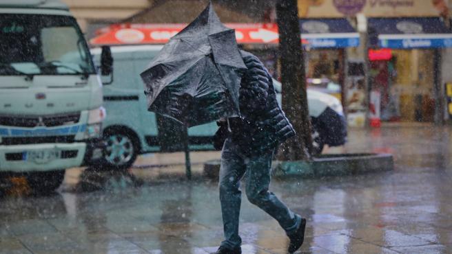 Una persona camina bajo la lluvia en un día con rachas de viento en Madrid.