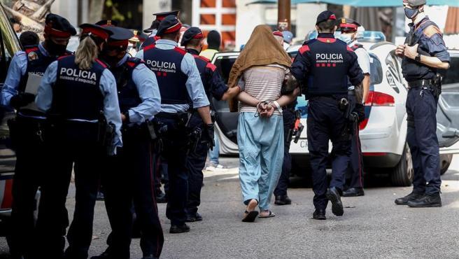 Agentes de los Mossos se llevan a uno de los detenidos en la operación.