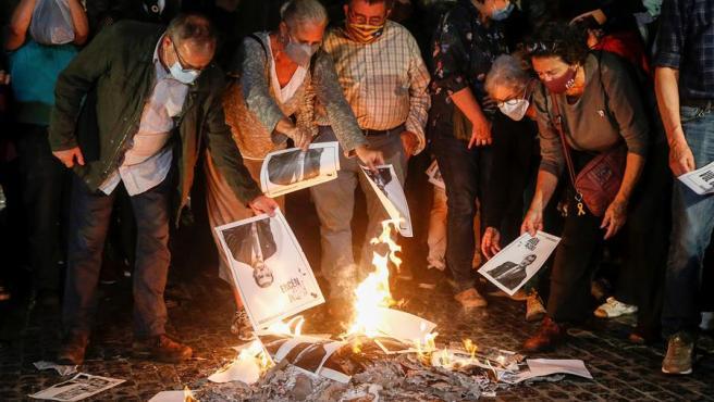 """Varias personas participan en la """"quema popular"""" de fotos del rey durante el acto organizado por la ANC en la víspera de la visita de Felipe VI a Barcelona."""