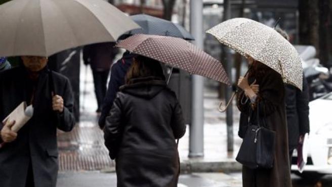 Imagen de archivo de personas con paraguas.