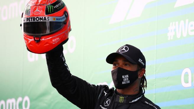 Lewis Hamilton sostiene un casco de Michael Schumacher