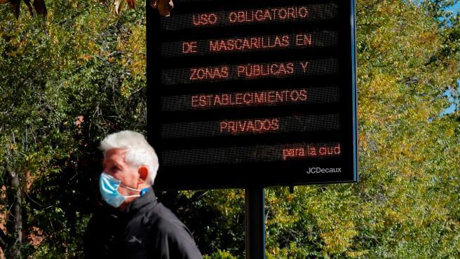 Un hombre pasa junto a un letrero con medidas contra el coronavirus en la Zona Básica de Salud de Valleaguado, en Coslada (Madrid).