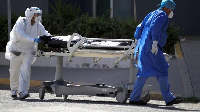 Personal médico traslada el cuerpo de un fallecido por COVID-19 en un hospital de Ciudad Juárez (México).