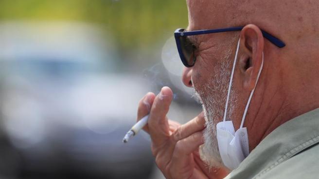 Un hombre con una mascarilla bajada fuma un cigarrillo.
