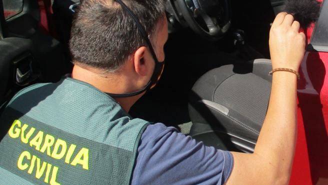 Un agente de la Guardia Civil inspecciona uno de los coches
