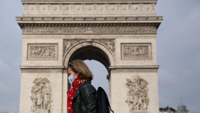 Una mujer con mascarilla frente el Arco de Triunfo de París.