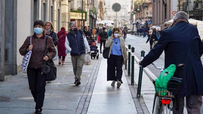 Viandantes con mascarillas pasean por las calles de Turín, Italia.