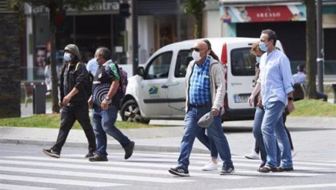 Personas con mascarilla pasean por una calle de Santander.