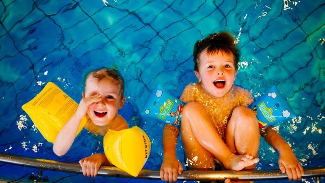 Dos niños en una piscina.