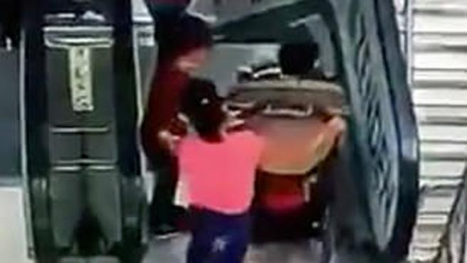 Un cámara de seguridad captó el momento en que una niña y un bebé, dentro de un carrito, se precipitan por una escalera mecánica en un centro comercial. El accidente tuvo lugar este domingo en Moscú, Rusia.