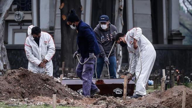 Trabajadores de un cementerio, con mascarillas por la pandemia del coronavirus, realizan un servicio fúnebre en Buenos Aires, Argentina.