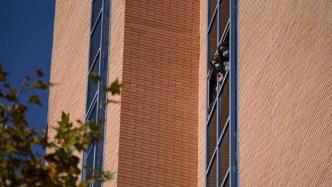 Dos estudiantes se asoman a una ventana de la residencia Galileo Galilei durante una concentración convocada por el sindicato 'Estudiantes en Lucha' en la residencia Galileo Galilei, en Valencia