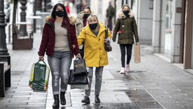 Dos personas usando mascarilla pasean por una ciudad española.