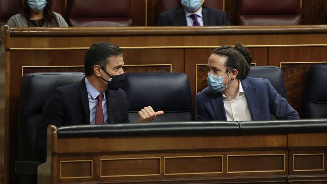 El presidente del Gobierno, Pedro Sánchez , y el vicepresidente segundo del Gobierno, Pablo Iglesias, conversan durante la presentación de la moción de censura de Vox en el Congreso.