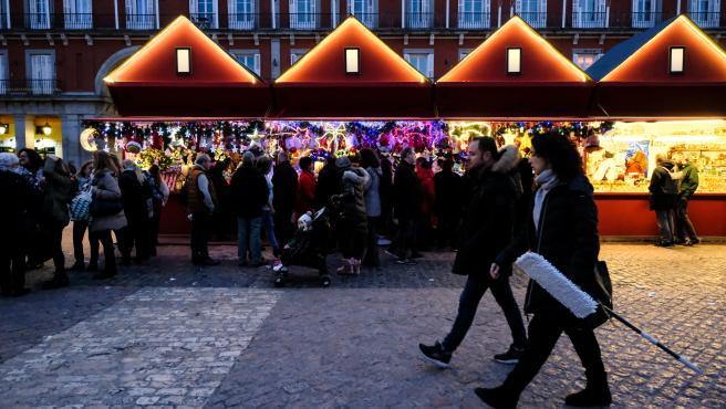 Turistas y vecinos de Madrid visitan los puestos del mercadillo navideño de la Plaza Mayor de Madrid.