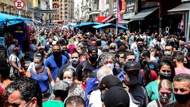 Transeúntes caminan por una calle comercial en el centro de Sao Paulo (Brasil), en plena pandemia de COVID-19.
