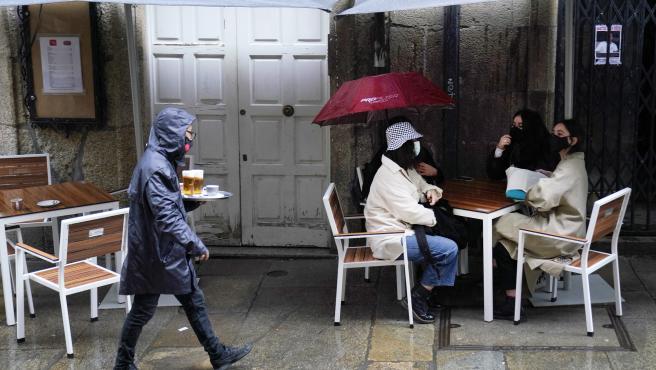 Covid 19 Santiago de Compostela entra en fase 3: locales de hostelería solo sirven en terrazas - terraza bar La Tita, atendiendo bajo la lluvia