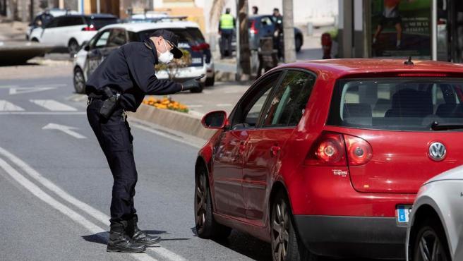 Un agente de policía detiene un vehículo en una calle de la localidad granadina durante un control del confinamiento.