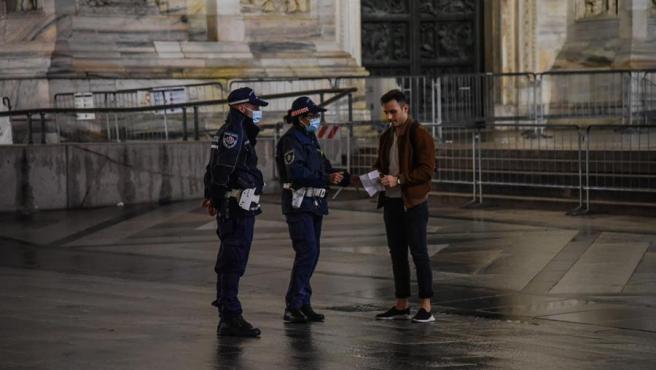 Agentes de policía piden la documentación a una persona, durante la primera noche del toque de queda impuesto en Milán, Italia, para frenar el avance de la pandemia del coronavirus.