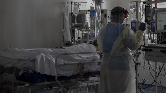 Un sanitario atiende a un paciente en la Unidad de Cuidados Intensivos (UCI)