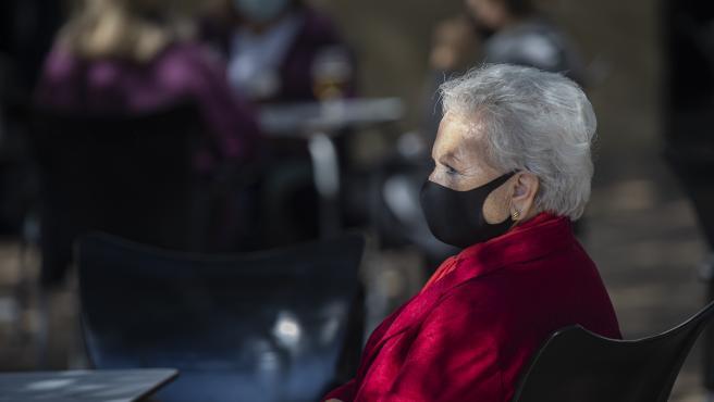 Una mujer mayor con mascarilla en la terraza de un bar