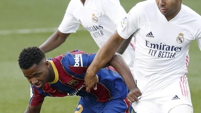 Ansu Fati intenta zafarse de Casemiro durante el Clásico.