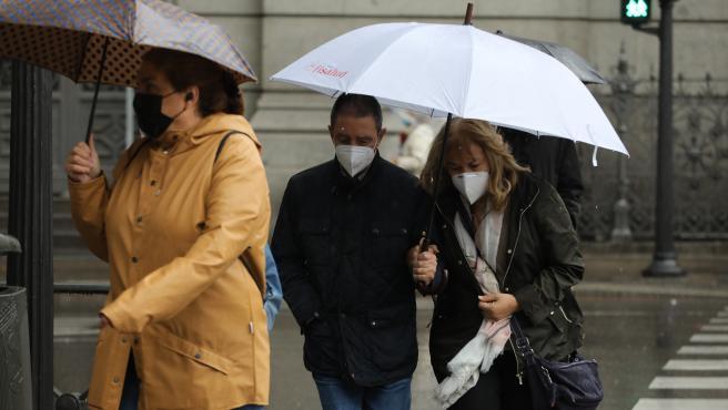 Transeúntes caminan en Madrid protegiéndose de la lluvia con paraguas.